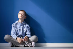 Thoughtful autistic boy. Sits with crossed legs on white floor against blue wall Stock Photos