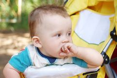 Thoughtful baby age of 9 months on baby carriage. Thoughtful baby boy age of 9 months on baby carriage Stock Photography