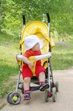 Thoughtful baby age of 9 months on baby carriage. Thoughtful nice baby age of 9 months on baby carriage Stock Image