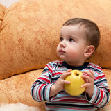 Thoughtful baby with apple Royalty Free Stock Images