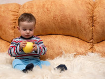 Thoughtful baby boy holding an apple Royalty Free Stock Photo