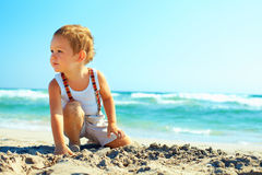 Thoughtful baby boy sitting on the beach Royalty Free Stock Image