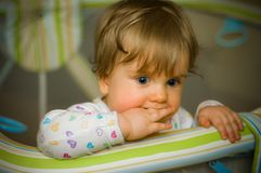 Thoughtful baby in playpen biting her fingers royalty free stock photos