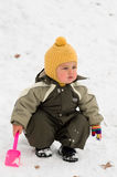 Thoughtful baby with shovel (winter) Royalty Free Stock Photography