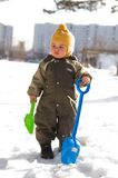 Thoughtful baby with shovels against buildings Royalty Free Stock Images
