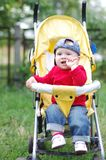 Thoughtful baby sitting on baby carriage Stock Photography