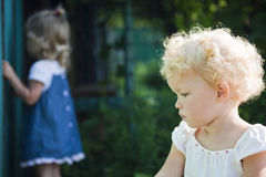The thoughtful baby and the spying baby stock photography