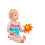 Thoughtful baby in swimsuit with pinwheel Royalty Free Stock Photography