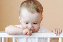 Thoughtful baby in white bed Royalty Free Stock Image