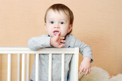 Thoughtful baby in white bed Royalty Free Stock Photos