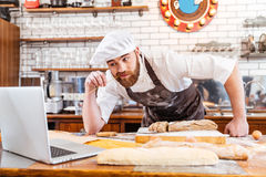 Thoughtful baker cutting bread and using laptop on kitchen Royalty Free Stock Photography