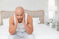 Thoughtful bald man sitting on bed Royalty Free Stock Photography