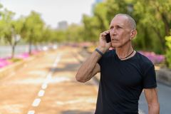 Thoughtful bald senior tourist man talking on mobile phone on th. E side of the street at peaceful park in Bangkok Thailand stock photos