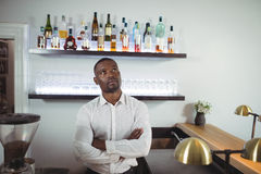 Thoughtful bar tender standing with arms crossed at bar counter Stock Photo
