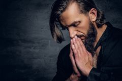 Thoughtful bearded male in black shirt. Close up studio portrait of thoughtful brutal bearded male in black shirt on grey background Royalty Free Stock Images