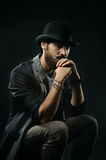 The thoughtful bearded man in a bowler hat clenched his hands in Royalty Free Stock Photo