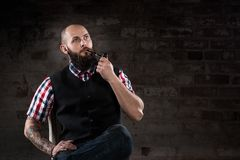 Thoughtful bearded man in a checkered shirt Stock Photos