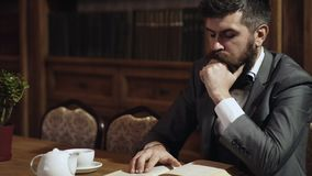 Thoughtful bearded man reads book in library while sitting at the table. Intelligent man in the library. Intelligent stock footage