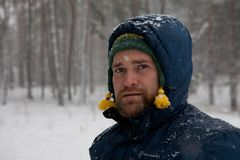 Thoughtful bearded man in snowy winter forest Royalty Free Stock Images