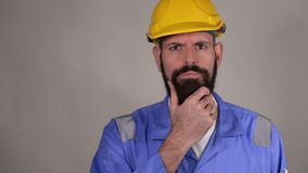 Thoughtful bearded middle age man in hard hat in the helmet touching his beard and thinking thoughts with smart face