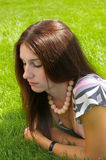 Thoughtful beautiful woman. Looking down to the green grass Stock Images