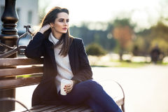 Thoughtful beautiful woman with cup of coffee sitting on a bench. In city street. Relax concept Stock Image