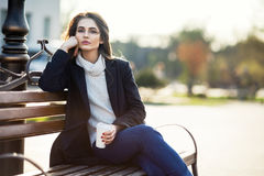 Thoughtful beautiful woman with cup of coffee sitting on a bench. In city street. Relax concept Royalty Free Stock Photography