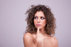 Thoughtful and beautiful woman with curly hair. Remember something, studio shot Stock Image
