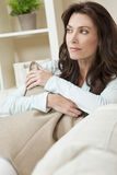 Thoughtful Beautiful Woman In Her Thirties. Indoor portrait of a beautiful young brunette woman in her thirties or forties holding a cushion and looking Stock Images