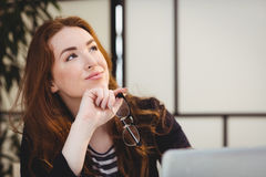 Thoughtful beautiful woman holding eyeglasses while looking up at creative office Stock Image