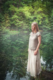 Thoughtful beautiful woman in long dress near river in forest. Outdoor Royalty Free Stock Photography