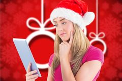 Thoughtful beautiful woman in santa hat using digital tablet. During christmas time Stock Photography
