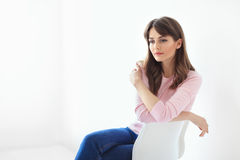 Thoughtful beautiful woman sitting on chair on white background Stock Photos