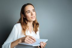Thoughtful beautiful woman taking notes. Sudden inspiration. Thoughtful beautiful nice woman holding her notebook and taking noted while being inspired Stock Images