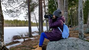 Thoughtful beautiful woman taking pictures in slowmotion of snow covered nature stock footage