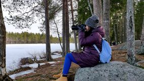 Thoughtful beautiful woman taking pictures in snow covered nature stock video footage