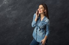 Thoughtful beautiful woman talking on phone. Modern lifestyle and communication. Pensive beautiful woman talking on phone at dark background with copy space Royalty Free Stock Images
