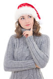 Thoughtful beautiful woman in winter clothes and santa hat dream. Ing isolated on white background Stock Photo