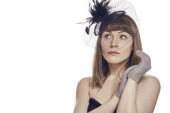 Thoughtful Beautiful Young Woman. Daydreaming. Thoughtful beautiful young woman with fringe haircut, bare shoulders, wearing black vintage feather light hat, net royalty free stock photos