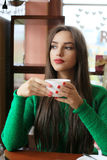 Thoughtful beautiful young woman drinking tea in cafe. Thoughtful beautiful young woman with long hair drinking tea in cafe Royalty Free Stock Photo