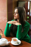 Thoughtful beautiful young woman drinking tea in cafe. Thoughtful beautiful young woman with long hair drinking tea in cafe Royalty Free Stock Images