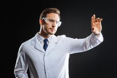 Thoughtful bespectacled scientist holding hand up and looking aside. Strange accident. Thoughtful bespectacled handsome scientist standing in the empty room Royalty Free Stock Photo