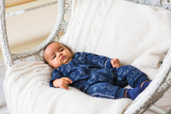 Thoughtful biracial mix of Hispanic and African American infant lying. Down on yellowish colored blanket Stock Photo