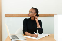 Thoughtful black businesswoman in glasses touching her neck looking away at desk with notepad and laptop in office Stock Photography