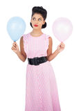 Thoughtful black hair model holding balloons Stock Image