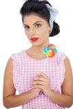 Thoughtful black hair model holding a colored lollipop Stock Photo