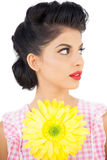 Thoughtful black hair model holding a flower and looking away. On white background Royalty Free Stock Photos