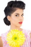 Thoughtful black hair model holding a flower and looking at came. Ra on white background Stock Photography