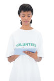 Thoughtful black haired volunteer using a tablet pc Stock Photos