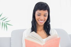 Thoughtful black haired woman in white clothes reading a book Stock Image